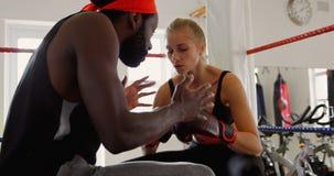 Instructor que ayuda al boxeador de sexo femenino en el ring de boxeo 4k metrajes