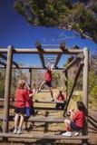 Instructor que ayuda a la muchacha para subir barras de mono durante el entrenamiento de la carrera de obstáculos imagenes de archivo