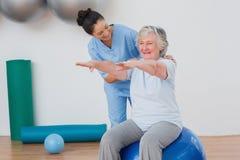 Instructor que ayuda a la mujer mayor en el ejercicio Foto de archivo