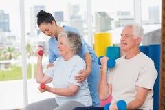 Instructor que ayuda a la mujer mayor en pesas de gimnasia de elevación del hombre Foto de archivo