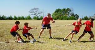 Instructor que ayuda a niños en esfuerzo supremo durante el entrenamiento de la carrera de obstáculos almacen de video
