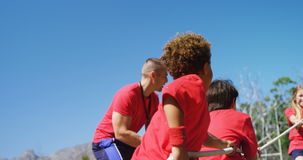 Instructor que ayuda a niños en esfuerzo supremo durante el entrenamiento de la carrera de obstáculos metrajes