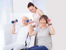 Instructor que ayuda a pares mayores con pesas de gimnasia Imagen de archivo libre de regalías