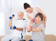 Instructor que ayuda a pares mayores con pesas de gimnasia Imágenes de archivo libres de regalías