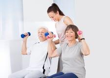 Instructor que ayuda a pares mayores con pesas de gimnasia Foto de archivo