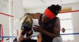 Instructor que consuela al boxeador de sexo femenino en el ring de boxeo 4k almacen de metraje de vídeo