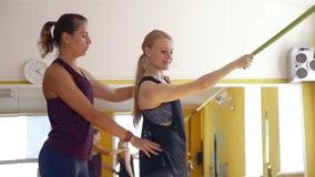 Instructor que da el entrenamiento de la mujer con la banda del ejercicio almacen de metraje de vídeo