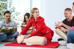 Instructor que demuestra el CPR en maniquí en la clase de los primeros auxilios foto de archivo