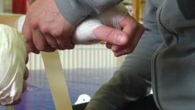 Instructor que envuelve los vendajes en la mano del boxeador antes de lucha 4K almacen de video