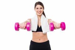 Instructor que lleva a cabo pesas de gimnasia en sus brazos extendidos Imágenes de archivo libres de regalías