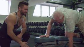 Instructor que mira cómo el cliente mayor hace ejercicios almacen de video
