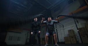 Instructor que supervisa el entrenamiento del hombre joven con la cuerda de la batalla almacen de metraje de vídeo