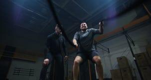 Instructor que supervisa el entrenamiento del hombre joven con la cuerda de la batalla metrajes