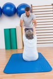 Instructor que trabaja con la mujer mayor en la estera del ejercicio Fotografía de archivo