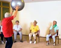 Instructor que trabaja con las señoras mayores en un gimnasio Imagen de archivo libre de regalías