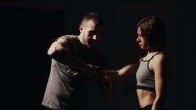 Instructor que venda sus manos con los vendajes antes de un boxeador de Dusko de la lucha en un fondo negro Prepárese para la bat almacen de metraje de vídeo