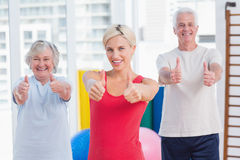 Instructor with senior couple showing thumbs up in gym. Portrait of confident female instructor with senior couple showing thumbs up in gym Royalty Free Stock Image