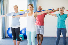 Instructor and seniors exercising with stretching bands stock image