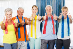 Instructor and seniors with thumbs up. During sports class Royalty Free Stock Image