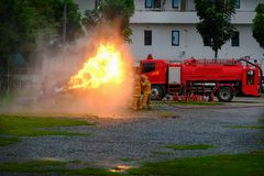 Instructor showing how to use a fire extinguisher on a training. Fire, Firemen using extinguisher and water from hose for fire fighting wearing a fire suit for Stock Images