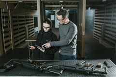 Instructor showing pistol to customer. In shooting range royalty free stock photos