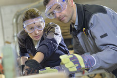 Instructor showing trainee carpentry work. Instructor showing trainee how to use sawing machine Royalty Free Stock Photography