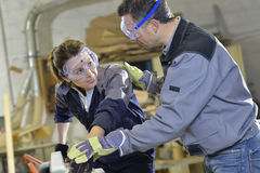 Instructor showing trainee carpentry work stock images