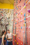 Instructor showing woman rock climbing wall Royalty Free Stock Photo