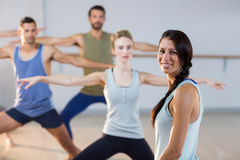 Instructor smiling at camera while students performing stretching exercise. In fitness studio Stock Images