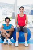 Instructor and smiling woman with exercise ball at gym Royalty Free Stock Photos