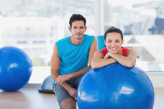 Instructor and smiling woman with exercise ball at gym Royalty Free Stock Photo