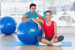 Instructor and smiling woman with exercise ball at gym Stock Photography