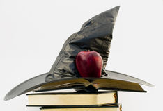 Instructor of Spells. Witch's black hat and red apple atop open gilt edged, leather cover books against white background Stock Images