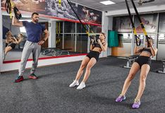 Suspension straps workout. Instructor and studends working with suspension straps in the gym Stock Photos