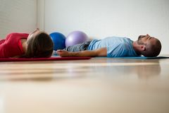 Instructor and student exercising while lying on mat in studio. Instructor and student exercising while lying on mat in yoga studio Stock Photography