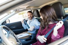 Instructor And Student Fastening Car Seatbelts. Smiling driving instructor teaching women to fasten seatbelt of car royalty free stock images