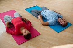 Instructor with student practicing reclined hero pose in yoga studio. High angle view of instructor with student practicing reclined hero pose in yoga studio Royalty Free Stock Photo