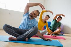 Instructor with students exercising at yoga studio. Male instructor with students exercising at yoga studio Royalty Free Stock Photography