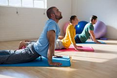 Instructor with students practicing cobra pose in yoga studio. Male instructor with students practicing cobra pose in yoga studio Stock Image