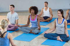 Instructor taking yoga class. In fitness studio stock image