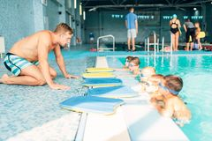 Instructor talking to children in the pool. Boys with swimming goggles ready for swimming and listening to trainer. Healthy activity in pool. Sportive kids Royalty Free Stock Photo