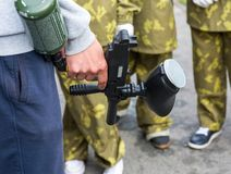 Instructor teaches boys how to play paintball. man holds paintball gun in hand stock images