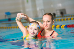Instructor teaches the girl swimming in a pool royalty free stock images