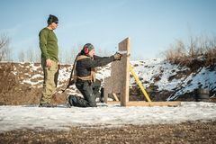 Instructor teaches student tactical gun shooting behind cover or barricade stock image