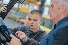 Instructor teaching apprentice how to drive heavy construction vehicle Royalty Free Stock Images