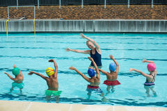 Instructor teaching children in swimming pool Stock Photography