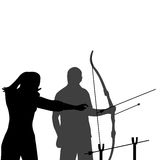 Instructor teaching a man how to shoot bow. A female instructor teaching a man how to shoot bow Royalty Free Stock Photo