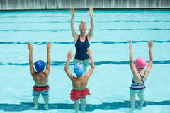 Instructor teaching students in swimming pool Royalty Free Stock Photos