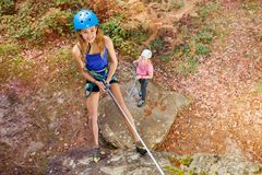 Instructor teaching teenager to abseil outdoors. Top view of female climbing instructor teaching teenage girl to abseil outdoors Royalty Free Stock Image