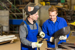Instructor teaching trainee how to weld metal Stock Photo